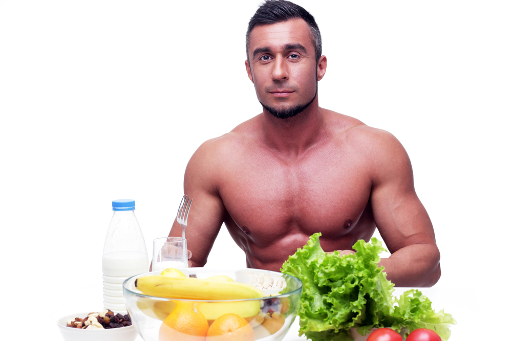 Handsome muscular man sitting at the table with healthy food