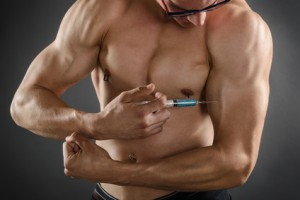 Close up of a muscular man injecting himself with steroids