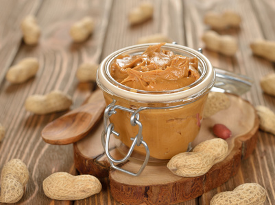 Peanut butter in a glass jar on a brown background