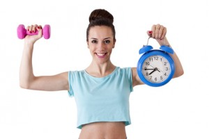 girl in the gym with weights and clock